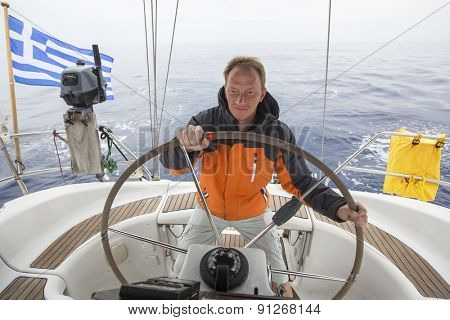 Young skipper drives the sailboat in the open sea. Yachting. Sailing.