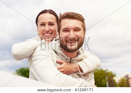 outdoor photo of smiley couple in love looking at camera and laughing