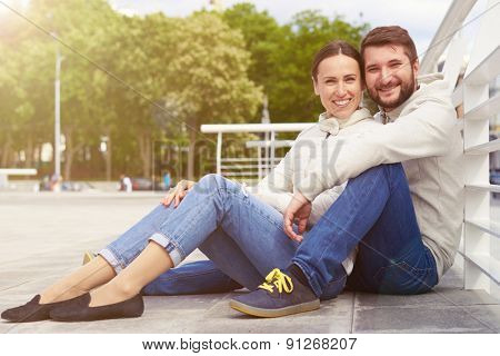 urban photo of smiley young couple sitting and looking at camera