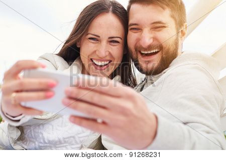 outdoor photo of happy laughing couple taking a selfie and looking at cellphone