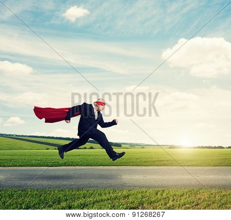 senior businessman wearing like superhero very fast running on the road over green fields and blue sky