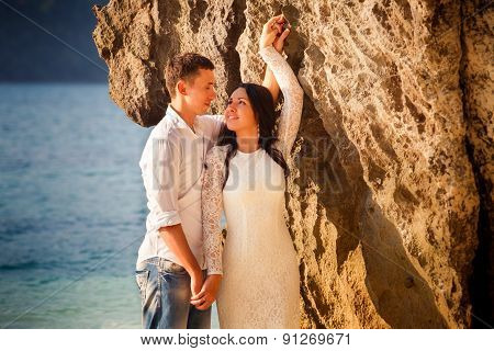 Bride And Groom Lean Against Rock