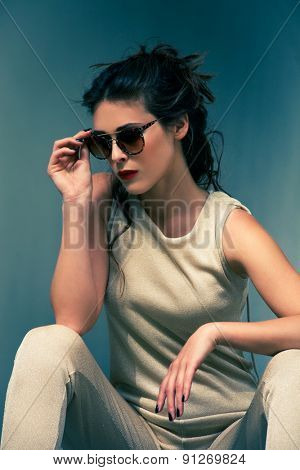 elegant summer fashion young woman wearing sunglasses and golden overalls, hair in bun, shot in the city