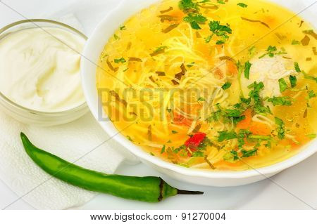 Zama, romanian and moldavian chicken soup with home-made noodles, served with green hot pepper and cream
