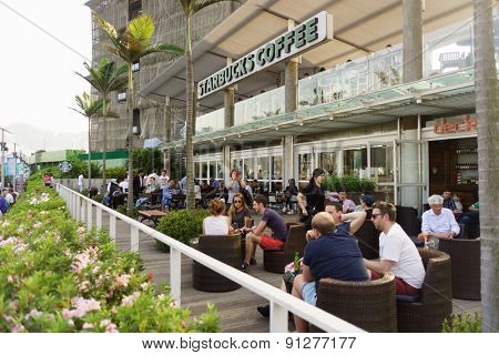 HONG KONG - APRIL 16, 2015: Starbucks cafe on Avenue of Stars. The Avenue of Stars, modelled on the Hollywood Walk of Fame, is located along the Victoria Harbour waterfront in Tsim Sha Tsui, Hong Kong