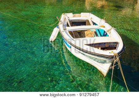 Empty white boat floating in clear water