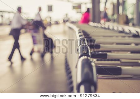 Close Up Trolleys Luggage With Blurred Of Passenger In Airport
