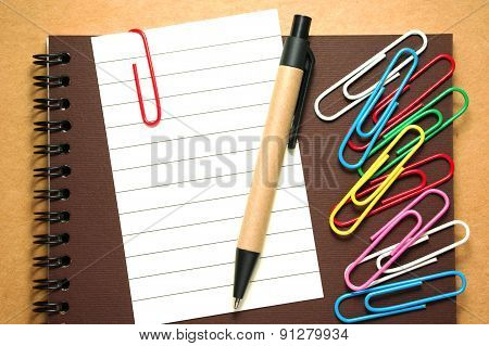 Note Paper With Pen And Paperclips On Notebook