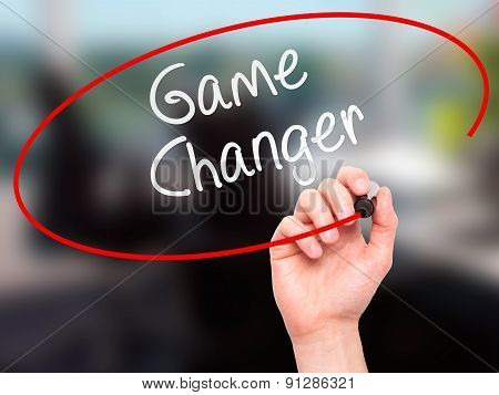 Man Hand writing Game Changer with marker on transparent wipe board.
