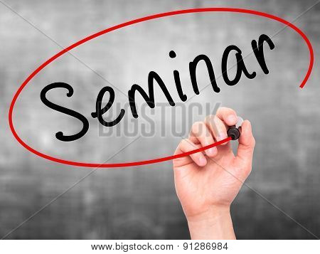 Man Hand writing Seminar with marker on transparent wipe board.