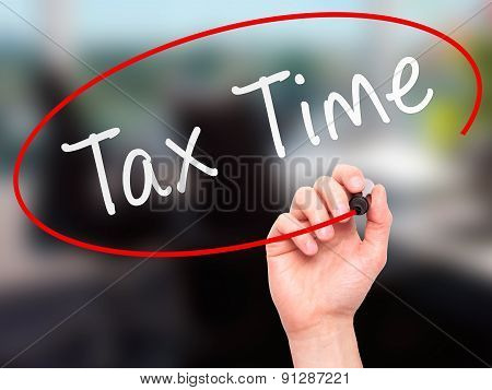 Man Hand writing Tax Time with marker on transparent wipe board.