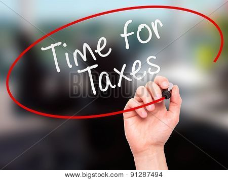 Man Hand writing Time for Taxes with marker on transparent wipe board.