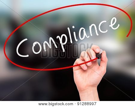 Man Hand writing Compliance with marker on transparent wipe board.