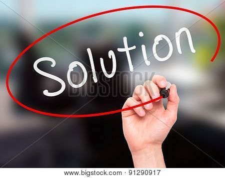 Man Hand writing Solution with marker on transparent wipe board.