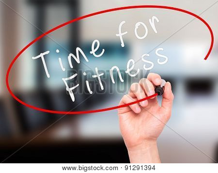 Man Hand writing Time for Fitness with marker on transparent wipe board.