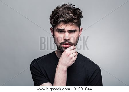Young handsome man doubting on gray background