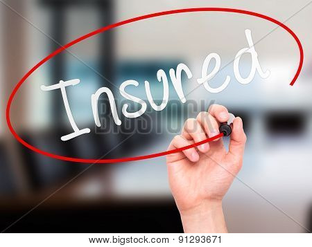 Man Hand writing Insured with marker on transparent wipe board.