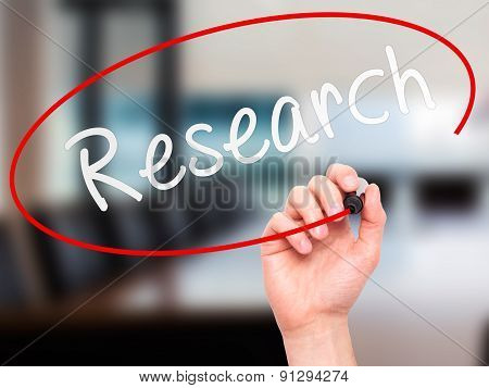 Man Hand writing Research with marker on transparent wipe board.