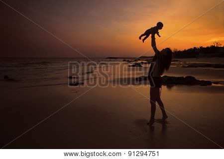 Silhouette of an Indian family enjoying in the beach during sunset