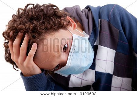 Young Boy With A Medical Mask, And The Hand On Head, Isolated On White Background, Studio Session