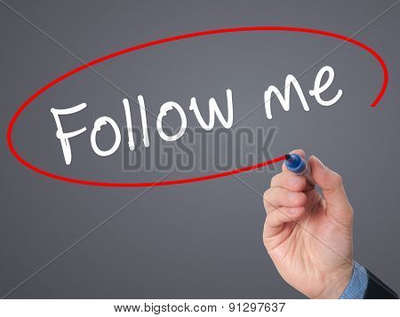 Man Hand writing Follow Me with marker on visual screen.