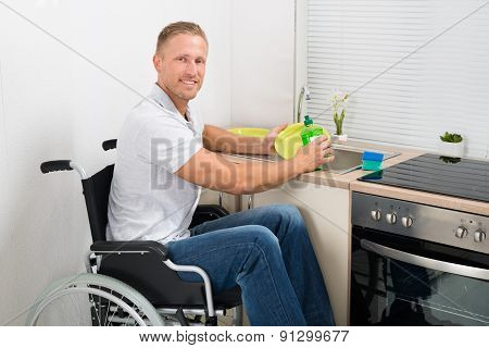 Disabled Man On Wheelchair Washing Dishes