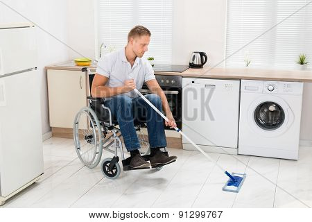 Disabled Man On Wheelchair Cleaning Floor