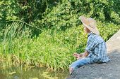 foto of rod  - Teenager with wooden rustic fishing rod is angling on concrete bridge - JPG