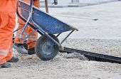 pic of wheelbarrow  - Construction worker pouring concrete from wheelbarrow to install drainage pipe in ground - JPG