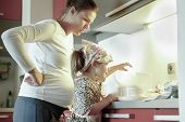 picture of experiments  - Pregnant mother and her daughter spending quality time together in the kitchen weighing ingredients for birthday cake having fun. Family values learning through experience concept. ** Note: Soft Focus at 100%, best at smaller sizes - JPG
