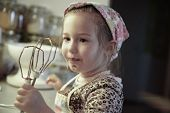 image of cake-mixer  - Little girl licking chocolate off the mixer beater after mixing dough for birthday cake - JPG