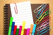 picture of marker pen  - Note paper clip on notebook with colorful marker pen and paperclips on brown cardboard background - JPG