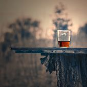pic of half  - glass half full on a wooden table outdoors in the evening