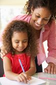 picture of homework  - Mother Helping Daughter With Homework At Home - JPG