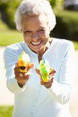 foto of pistol  - Senior Woman Shooting Water Pistols - JPG