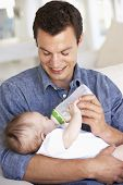 picture of feeding  - Young Father With Baby Feeding On Sofa At Home - JPG