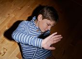 foto of child abuse  - Child abuse composition of a frightened young boy sitting on the wooden floor in a light of a flashlight circle - JPG