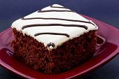 picture of auburn  - Red velvet cake with white icing and drizzles of chocolate placed on square red plate on black background - JPG