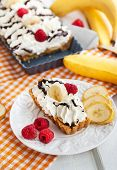 image of banana  - Banoffee pie (banana and toffee) decorated with whipped cream and fresh banana and raspberry