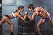 picture of conflict couple  - Athlete muscular sportsmen man and woman with hands clasped arm wrestling challenge between a young couple Crossfit fitness sport training lifestyle bodybuilding concept - JPG