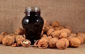 foto of walnut  - Jam from young walnuts in glass jar and walnuts - JPG