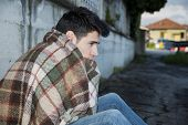 stock photo of beggar  - Young male beggar on city sidewalk with blanket on his shoulders - JPG