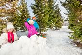 pic of snow forest  - Girls and boy playing snowball fight game behind snow fortress together standing behind the snow wall with fir forest on the background during winter day - JPG
