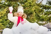 foto of snow forest  - Laughing small girl with snow ball stands behind the snow wall with forest on the background - JPG