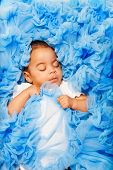image of babygro  - Chubby African small baby laying and sleeping on the blue cloth close - JPG