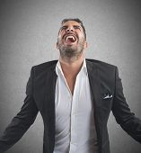 stock photo of scream  - Anxious businessman stressed out from work screams - JPG