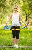 foto of hula hoop  - Beautiful sporty girl standing on the mat in park and holding hula hoop - JPG