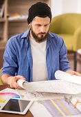 foto of draft  - Male designer dressed casual sitting at the table and looking at draft Designer - JPG