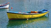 pic of old boat  - Old fishing rowing boat painted in yellow on the water on a sunny summer day - JPG