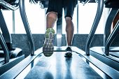 pic of treadmill  - Legs of sportsman running on treadmill - JPG
